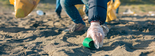 Young girl picking up rubbish on a beach