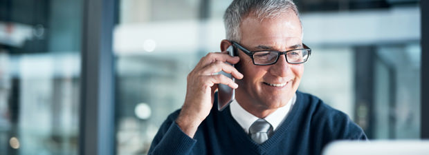 Man in office smiling and speaking into telephone