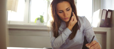 Woman talking on mobile phone in home office