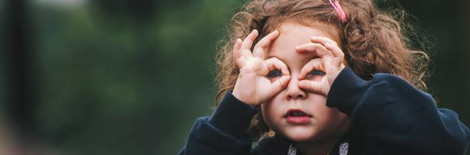 Little girl looking through her fingers